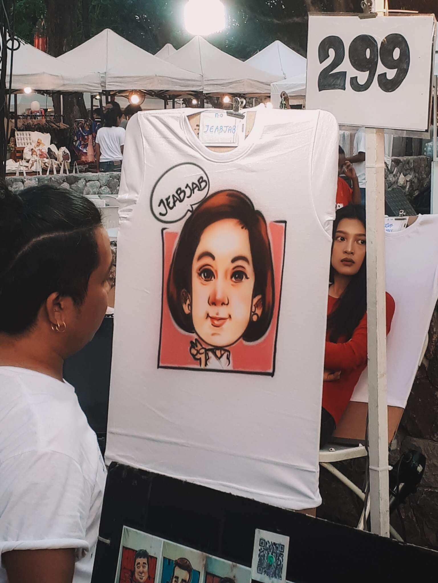 artist painting a face on a t-shirt at cicada market that he sells