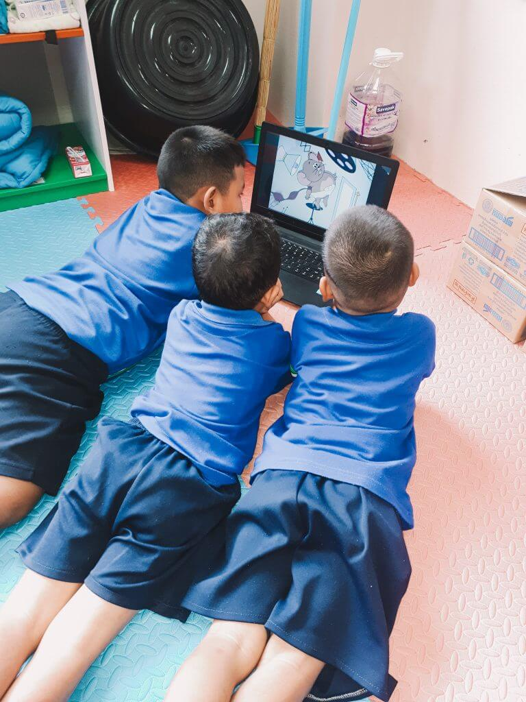 three boys watching Tom and Jerry off of Teacher Chanes laptop