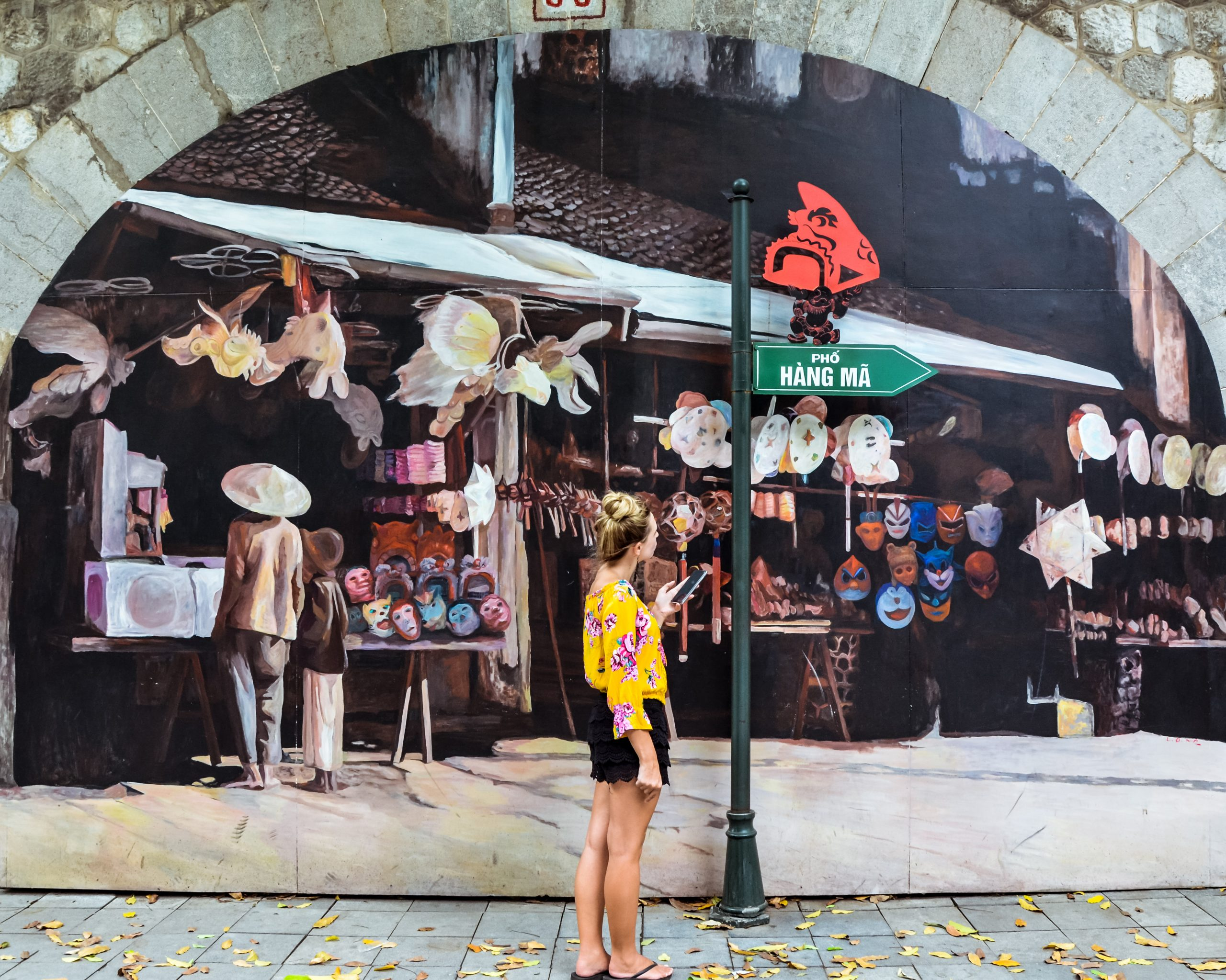 a girl with a yellow shirt is enjoying the street murals in Hanoi, Vietnam