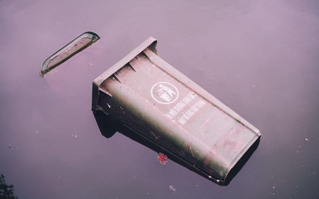 dustbin in dirty brown water
