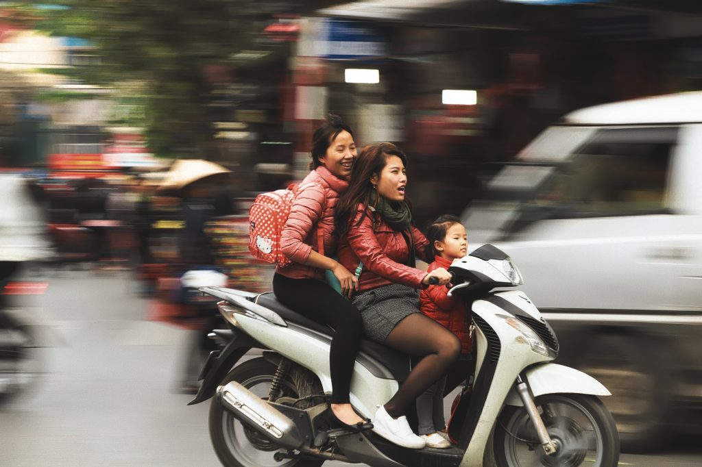 two woman and a little girl riding a scooter in Vietnam