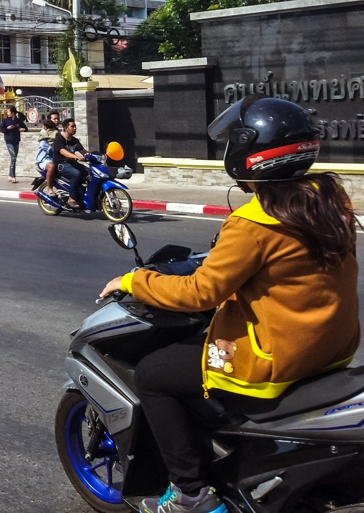 a thai lady taking a ride on her scooter during the day