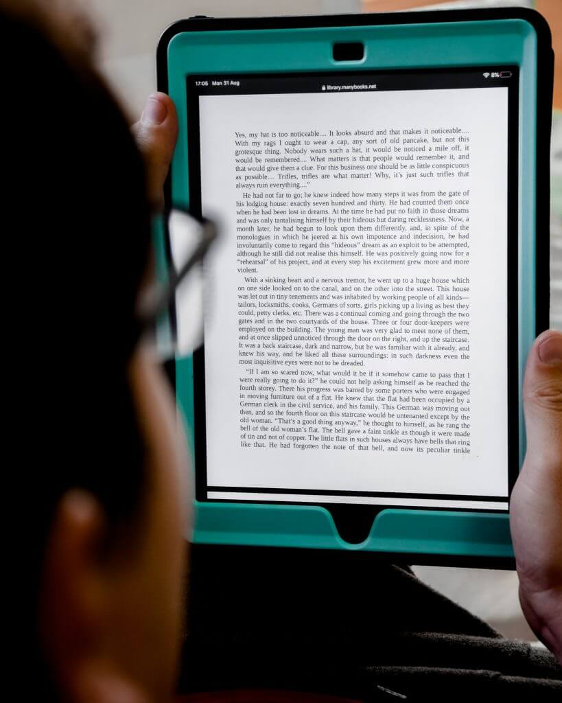 Man reading an ebook on his Ipad. Write an ebook to make money online.